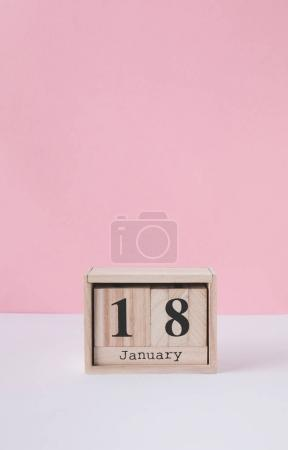 close up view of wooden calendar isolated on pink