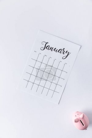 top view of part of calendar with january lettering and piggy bank isolated on white