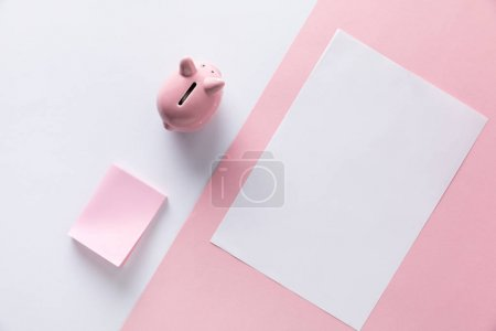 top view of pink piggy bank, empty sticky notes and paper