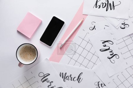 flat lay with calendar, smartphone, cup of coffee and sticky notes isolated on white