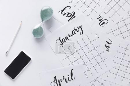 flat lay with calendar, smartphone, pencil and sand clock isolated on white