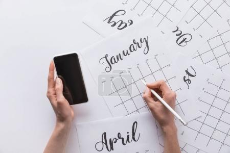 partial view of woman with smartphone in hand making notes in calendar isolated on white