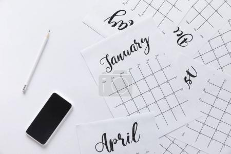 flat lay with calendar, smartphone and pencil isolated on white
