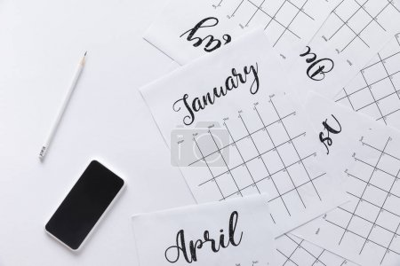 Photo for Flat lay with calendar, smartphone and pencil isolated on white - Royalty Free Image