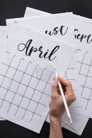 partial view of woman making notes in calendar isolated on black