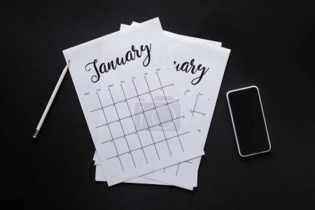 flat lay with paper calendar, smartphone and pencil isolated on black