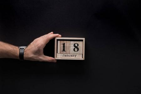 cropped shot of man holding wooden calendar isolated on black