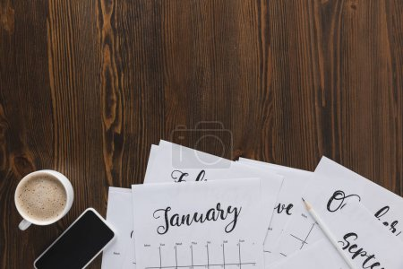 flat lay with paper calendar papers, smartphone and cup of coffee on wooden tabletop