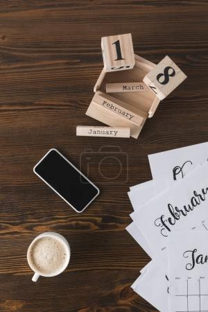 top view of arranged smartphone, cup of coffee, calendar parts on wooden surface