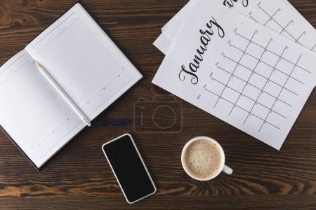 Photo pour Lay plat avec bloc-notes vide, calendrier, crayon et intelligent sur la surface en bois - image libre de droit