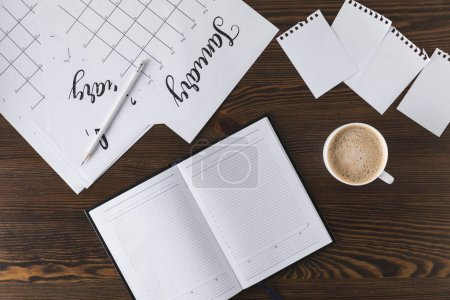 Photo for Flat lay with empty notebook, calendar and cup of coffee on wooden surface - Royalty Free Image