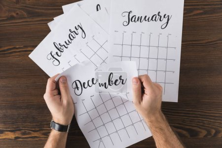 cropped shot of man tearing calendar on wooden tabletop