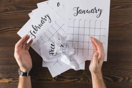 cropped shot of male hands and teared calendar on wooden tabletop