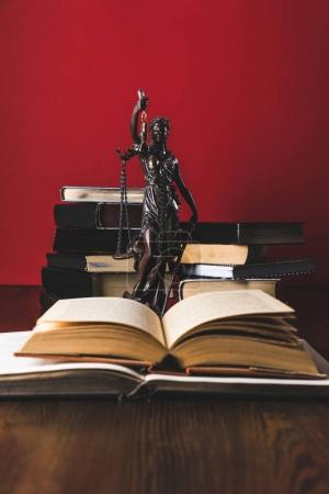 Photo pour Ouvert de livres juridiques avec Dame justice statue sur la table en bois, la notion de droit - image libre de droit