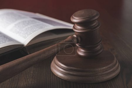 opened juridical book with hammer on wooden table, law concept