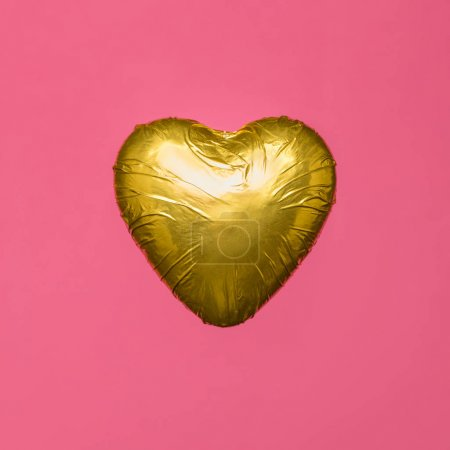 heart shaped candy in golden wrapper isolated on pink