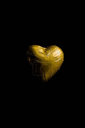 Photo for Heart shaped candy in golden wrapper isolated on black - Royalty Free Image