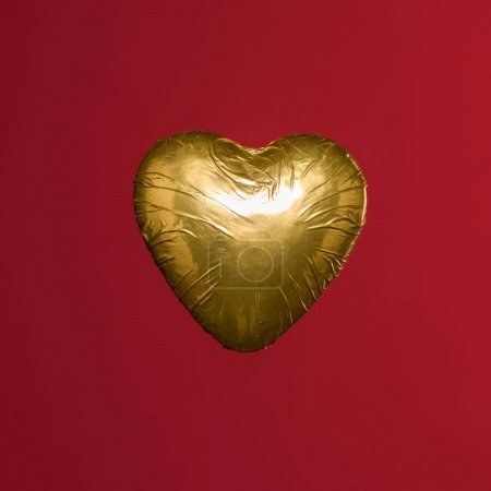 heart shaped candy in golden wrapper isolated on red