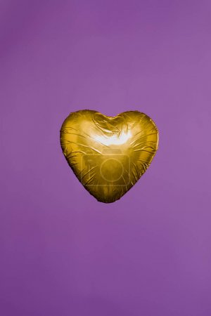 heart shaped candy in golden wrapper isolated on purple