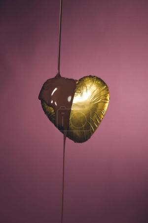 heart shaped candy in golden wrapper with liquid chocolate isolated on pink
