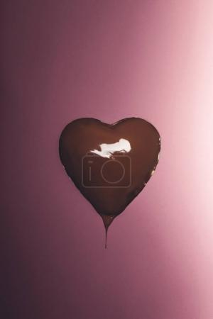 heart shaped candy with liquid chocolate isolated on pink