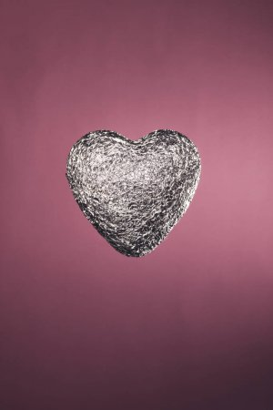 Photo for Heart shaped candy in silver wrapper isolated on pink - Royalty Free Image