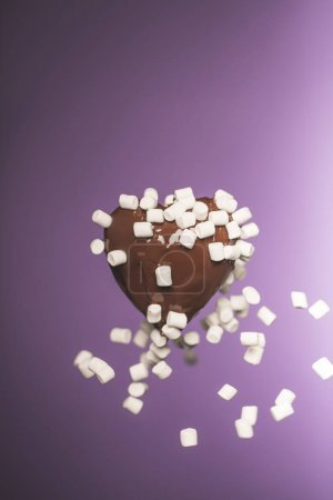 chocolate heart shaped candy with falling marshmallow isolated on purple