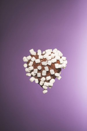 chocolate heart shaped candy with marshmallow isolated on purple