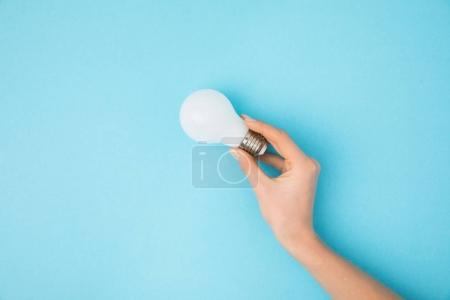 partial view of woman holding light bulb in hand isolated on blue