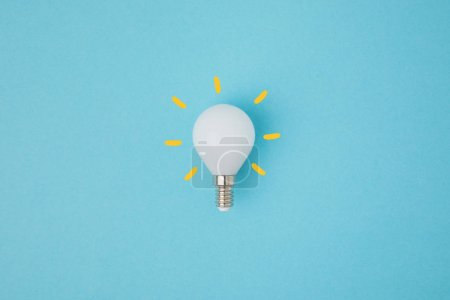 Photo for Close up view of white light bulb with yellow lines isolated on blue - Royalty Free Image