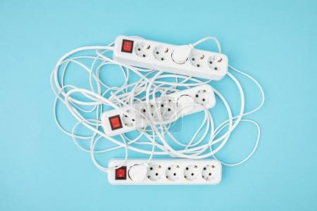 top view of arrangement of extension cords isolated on blue