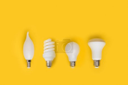 Photo for Top view of set of different white lamps isolated on yellow - Royalty Free Image