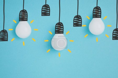 Foto de Cerrar vista de lámparas blancas simulando colgar en portalámparas aislados en azul - Imagen libre de derechos
