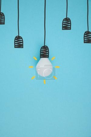 top view of light bulb pretending hanging on lamp holder isolated on blue