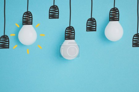 close up view of white lamps pretending hanging on lamp holders isolated on blue