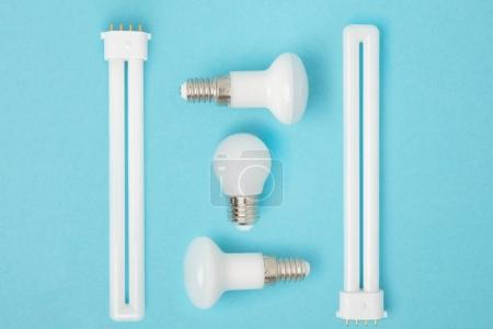 flat lay with arranged various light bulbs isolated on blue