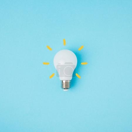 Foto de Cerrar vista de bombilla de luz blanca con líneas amarillas aisladas en azul - Imagen libre de derechos