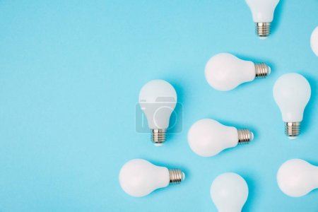 Photo for Flat lay with arranged white light bulbs isolated on blue - Royalty Free Image