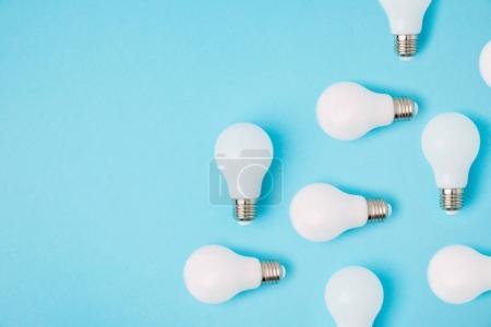 Photo pour Pose plate avec des ampoules blanches disposées isolées sur bleu - image libre de droit
