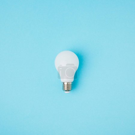 Photo for Close up view of white light bulb isolated on blue - Royalty Free Image