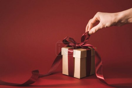 Photo for Partial view of woman holding ribbon on gift box on red - Royalty Free Image