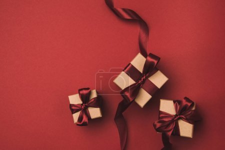 flat lay with arrangement of gifts decorated with ribbons isolated on red