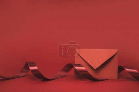 Photo for Close up view of envelope and ribbon isolated on red - Royalty Free Image