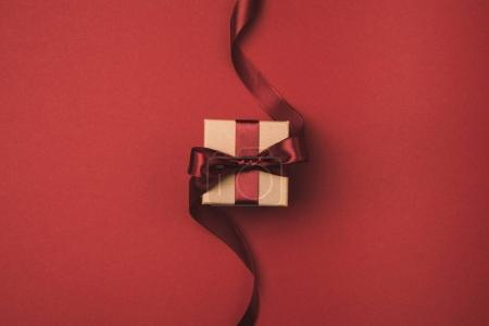 Photo for Top view of gift box decorated with ribbon isolated on red - Royalty Free Image