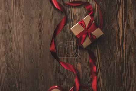 flat lay with present and red ribbon on wooden tabletop