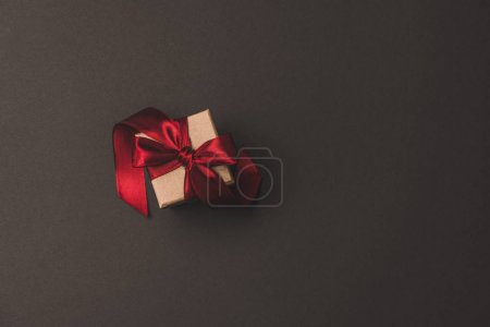 top view of gift box with red ribbon isolated on dark surfae