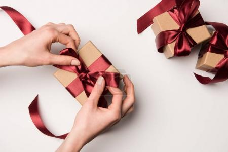 partial view of woman tying ribbon on gift box isolated on white