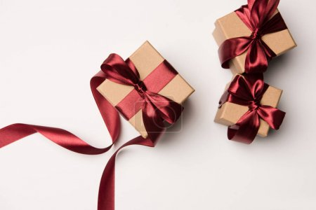 top view of arranged gift boxes with red ribbons isolated o white