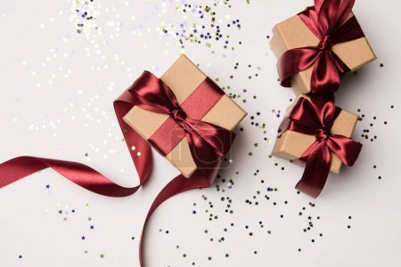 top view of arranged gifts with red ribbons and confetti isolated on white