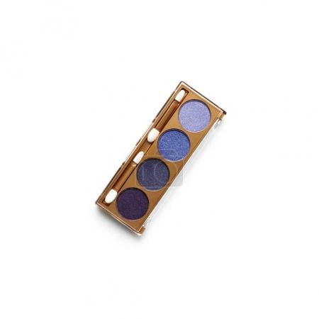 top view of container with different shaded purple cosmetic eye shadows isolated on white